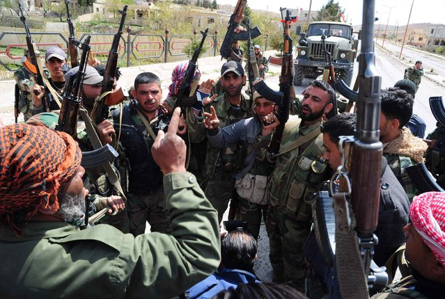 Members of the Syrian government forces celebrate in al-Sarkha village, in the Qalamun mountains, northeast of Damascus, after taking control of the village from rebel fighters, on April 14, 2014. Government forces took control of al-Sarkha in the morning before moving in to recapture the ancient Christian town of Maalula. (Photo by AFP Photo/STR)