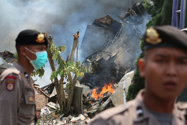 Indonesian police secure the scene where an Indonesian military C-130 Hercules crashed into a residential area in Medan on June 30, 2015. (Photo by Kharisma Tarigan/AFP Photo)