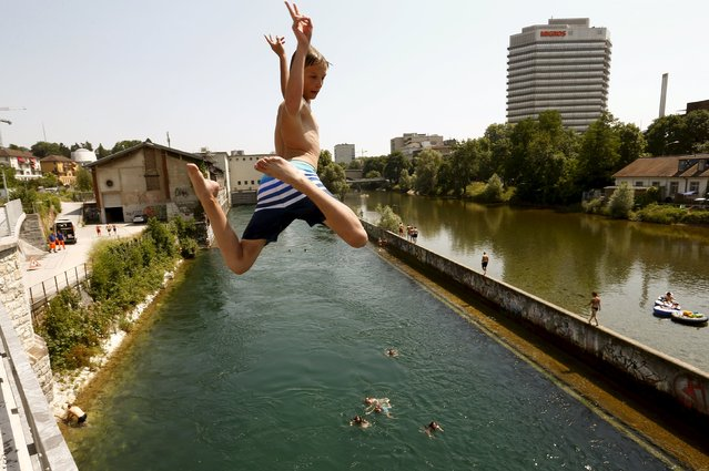 A boy jumps during hot temperatures from a bridge into the Limmat river in Zurich July 3, 2015. On the right is the Sihl river and the headquarters of Swiss retailer Migros. (Photo by Arnd Wiegmann/Reuters)