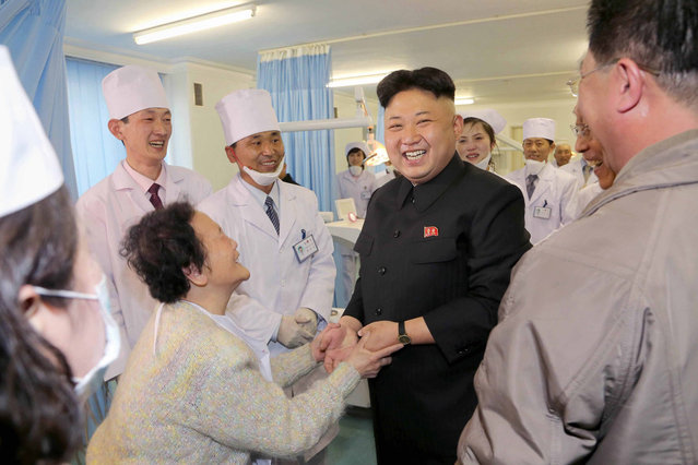 This undated picture released by North Korea's official Korean Central News Agency (KCNA) on March 22, 2014 shows North Korean leader Kim Jong-Un (centre R) being greeted during a visit to the Ryugyong Dental Hospital in Pyongyang. (Photo by AFP Photo/KCNA via KNS)