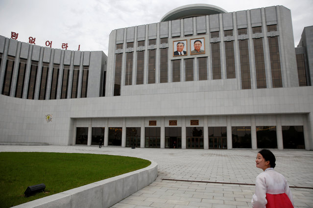 A guide leads visitors towards the Mangyongdae Children's Palace decorated with pictures of former North Korean leaders Kim Il Sung and Kim Jong Il in central Pyongyang, North Korea May 5, 2016. (Photo by Damir Sagolj/Reuters)