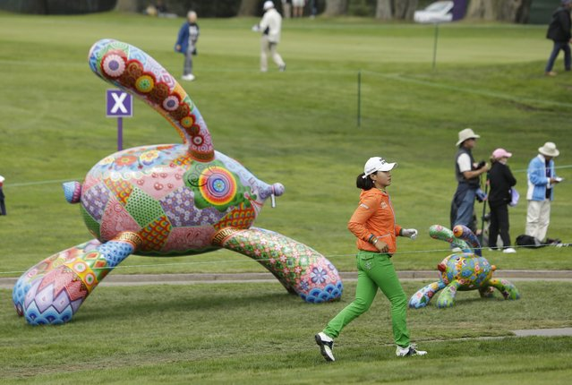 Hee Young Park, foreground, of South Korea, runs up to view the 18th green before hitting from the fairway at the Lake Merced Golf Club during the first round of the Swinging Skirts LPGA Classic golf tournament on Thursday, April 24, 2014, in Daly City, Calif. (Photo by Eric Risberg/AP Photo)