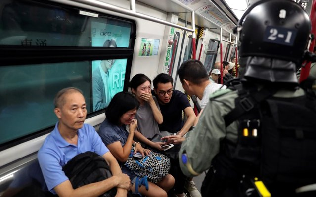 Commuters react as police officers looking for protestors raid a metro train, in Hong Kong, China on September 1, 2019. (Photo by Danish Siddiqui/Reuters)