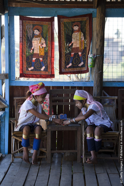 Burmese Long Neck children play as they wait for tourists to arrive at a handicraft shop on Inle Lake