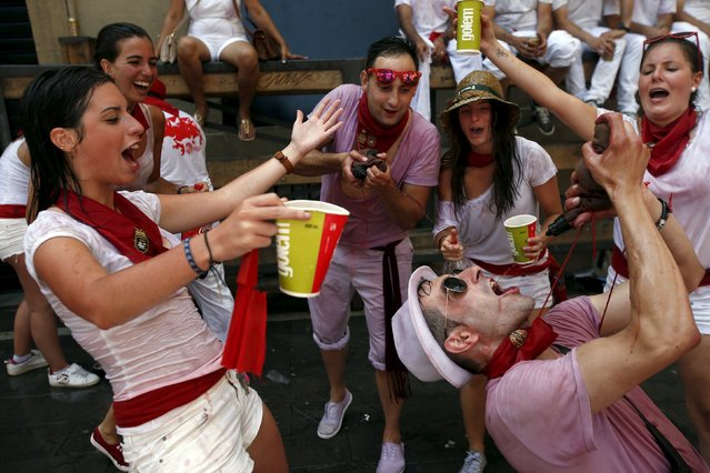 Revellers drink during the start of the San Fermin Festival in Pamplona, Spain, July 6, 2015. (Photo by Susana Vera/Reuters)