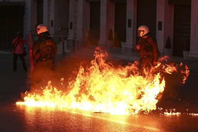 A petrol bomb explodes in front of policemen during clashes in Athens, on Sunday, May 8, 2016. Protesters in Greece have hurled firebombs and other projectiles at police in front of parliament before a controversial vote on an austerity bill. (Photo by Yorgos Karahalis/AP Photo)