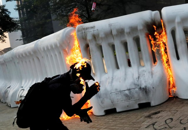 An anti-government protester catches fire after throwing Molotov cocktail during a demonstration near Central Government Complex in Hong Kong, China, September 15, 2019. (Photo by Tyrone Siu/Reuters)