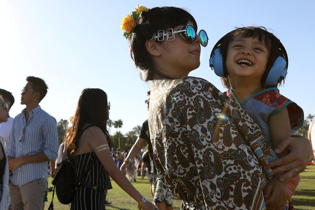 A child basks in the knowledge that she cannot hear the sound of EDM and cackling celebrities on the opening day of the Coachella Valley Music and Arts Festival on April 15, 2017 in Indio, California. (Photo by Carlo Allegri/Reuters)