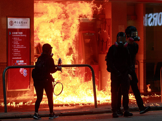 Protesters burn Bank of China's ATM with a petrol bomb in Hong Kong, China on October 1, 2019. (Photo by Kevin On Man Lee/Penta Press/Rex Features/Shutterstock)