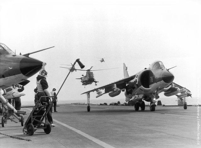 A Sea Harrier jump jet on the flight deck of HMS Hermes heading to the Falklands after the Argentinian invasion of the islands, April 1982. A Sea King helicopter hovers in the background