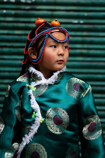 """Losar Girl"". During a trip to northern india I joined a losar celebration, the tibetan new year. This is a portrait of a tibetan girl in a traditional dress. Photo location: McLeod Ganj, India. (Photo and caption by Matthias Troeger/National Geographic Photo Contest)"