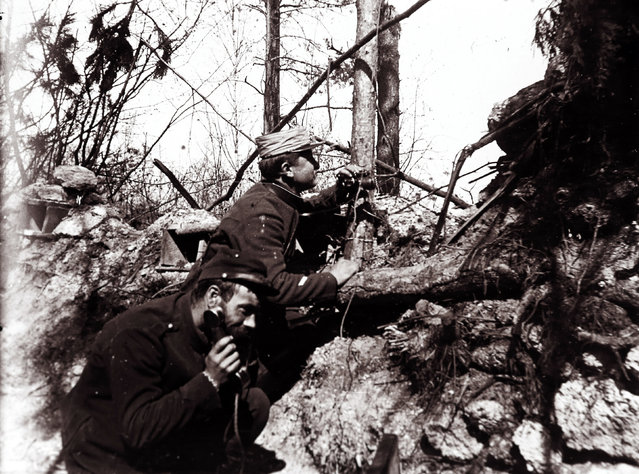 An undated archive picture shows French artillery officers on the phone relaying instructions to adjust cannon fire in a trench on the front line, at an unknown location in France. (Photo by Collection Odette Carrez/Reuters)