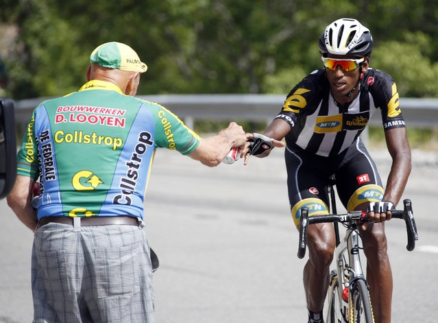 MTN-Qhubeka rider Daniel Teklehaimanot of Eritrea receives drink from a spectator as he climbs the Allos pass during the 161-km (100 miles) 17th stage of the 102nd Tour de France cycling race from Digne-les-Bains to Pra Loup in the French Alps mountains, France, July 22, 2015. (Photo by Eric Gaillard/Reuters)