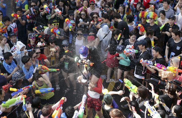 Participants spray water guns at each other during the 3rd Water Gun Festival in Seoul, South Korea, Sunday, July 26, 2015. Thousands of people enjoyed the annual festival which is held from July 25 to July 26 to avoid the summer heat. (Photo by Lee Jin-man/AP Photo)