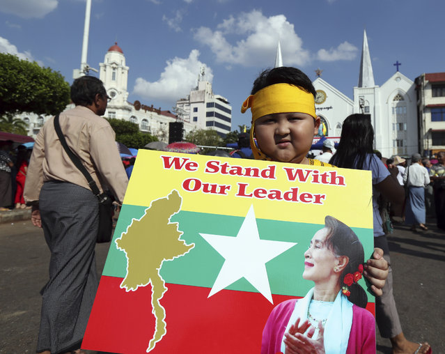 A boy with Karen ethnic attire holds placard with picture of Myanmar leader Aung San Suu Kyi during a rally Sunday, December 1, 2019, in Yangon, Myanmar. About 700 people rallied Sunday to show support for Myanmar's leader, Aung San Suu Kyi, as she prepares to defend the country against charges of genocide at the U.N.'s highest court. (Photo by Thein Zaw/AP Photo)