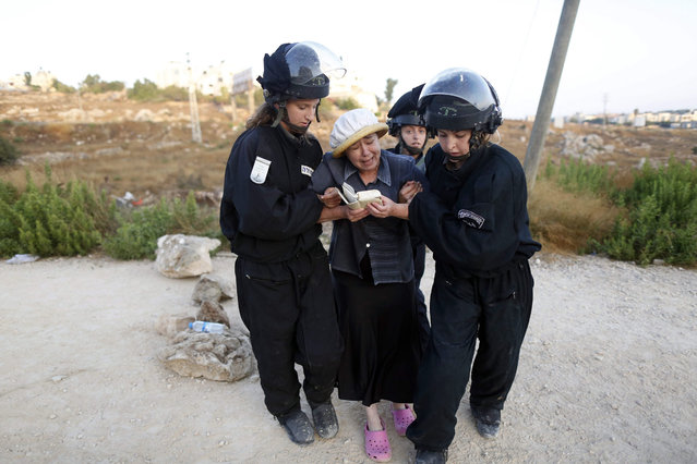 Female Israeli security forces drag away an Israeli settler woman during the evacuation of a 24 housing units illegal building site where settlers had barricaded at the Jewish settlement of Beit El, near the West Bank town of Ramallah, early 28 July 2015. Israel's Supreme Court earlier had ruled to demolish the 24 housing units in the settlement claiming  they were illegally built on private Palestinian land. (Photo by Abir Sultan/EPA)