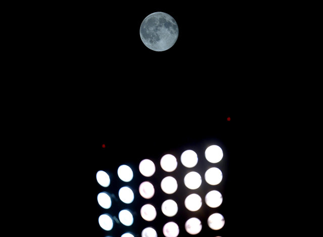 A blue moon rises behind the US Cellular Field lights during the eighth inning of a baseball game between the Chicago White Sox and the New York Yankees in Chicago, Friday, July 31, 2015. A blue moon happens when the moon rises in its full stage twice during the same month. (Photo by Jeff Haynes/AP Photo)