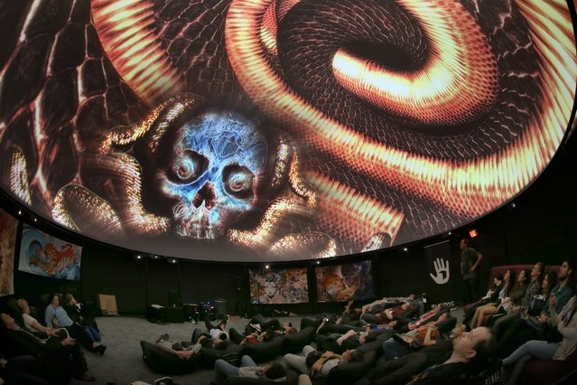 Attendees view a presentation in the Fulldome Pro display of a 360 video projection at the E3 (Electronic Entertainment Expo) in Los Angeles, California, USA, 14 June 2016. The E3 expo introduces new games and gaming devices and is an anticipated annual event among gaming enthusiasts and marketers. The event runs from 14 to 16 June 2016. (Photo by Mike Nelson/EPA)
