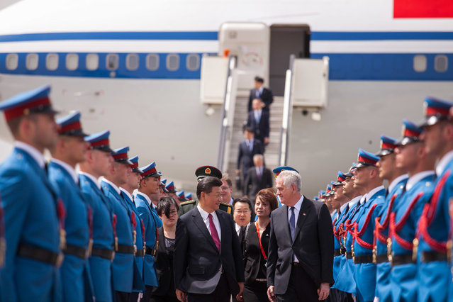 In this photo provided by the Serbian Presidential Press Service, Chinese President Xi Jinping, center left, and his Serbian counterpart, Tomislav Nikolic, center right, pass by Serbian army Honor Guards upon Xi's arrival to Belgrade, Serbia, Friday, June 17, 2016. Xi arrived in Serbia on Friday for a visit meant to boost relations with the friendly nation and assert China's intention to increase its presence in the Balkans and Europe. (Photo by Serbian Presidential Press Service via AP Photo)
