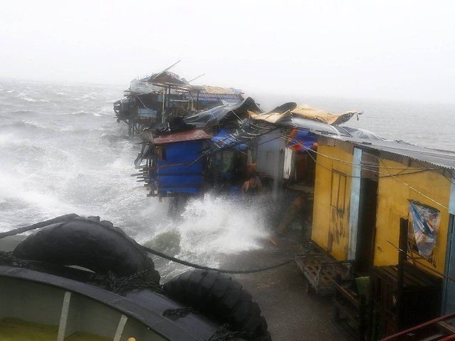 Abandoned homes are hit by waves after they were left behind by their Filipino resident in the strong winds and rain brought by typhoon Rammasun along the coastline of the Tondo slum area, in Manila, Philippines, 16 July 2014. (Photo by Dennis M. Sabangan/EPA)