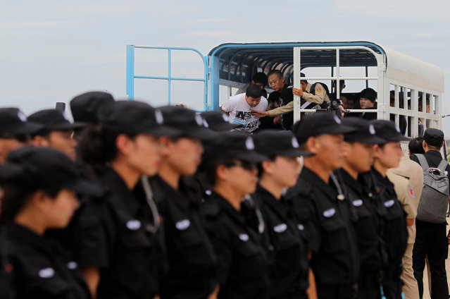 The Chinese police SWAT team lines up as suspects of telecom fraud arrive before their deportation to China at the International Airport of Phnom Penh, Cambodia June 24, 2016. (Photo by Samrang Pring/Reuters)