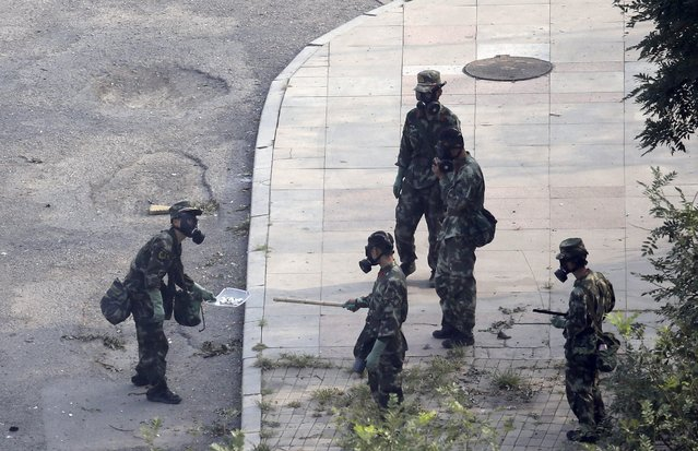 Paramilitary policemen in gas masks examine unknown chemicals at a square near the site of Wednesday night's explosions at Binhai new district in Tianjin, China, August 15, 2015. (Photo by Jason Lee/Reuters)