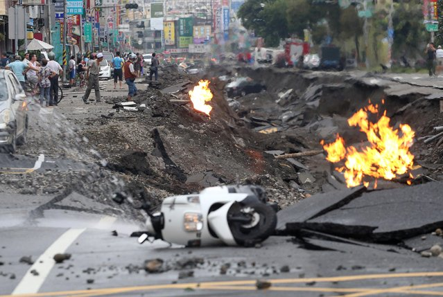 Vehicles are left lying on a destroyed street as part of the street is burning with flame following multiple explosions from an underground gas leak in Kaohsiung, Taiwan, early Friday, August 1, 2014. Several underground gas explosions ripped through Taiwan's second-largest city overnight, hurling concrete through the air and blasting long trenches in the streets, authorities said Friday. (Photo by AP Photo)