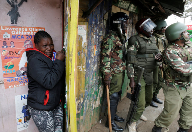 A woman cries as she stand behind policemen during clashes between supporter of opposition leader Raila Odinga and policemen in Kibera slum in Nairobi, Kenya, August 12, 2017. (Photo by Goran Tomasevic/Reuters)