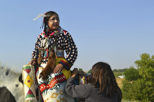 In this Friday, August 18, 2017 photo, Julia Brien, left, prepares for the Crow Fair parade in Crow Agency, Mont. For the Crow Tribe, the eclipse coincides with the Parade Dance at the annual Crow Fair, marking the tribe's new year. (Photo by Mary Hudetz/AP Photo)