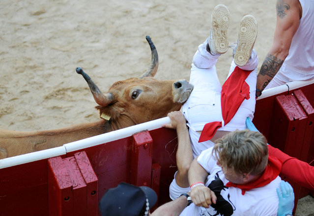 A reveller is tossed by a wild cow after the first running of the bulls at the San Fermin festival in Pamplona, northern Spain, July 7, 2016. (Photo by Eloy Alonso/Reuters)