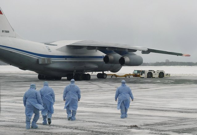 Medical staff members walk towards a military plane, which evacuated citizens of Russia and ex-Soviet countries from China's Wuhan province, at the Roshchino International Airport outside Tyumen, Russia, February 5, 2020. (Photo by Yuri Shestak/Vsluh.ru via Reuters)