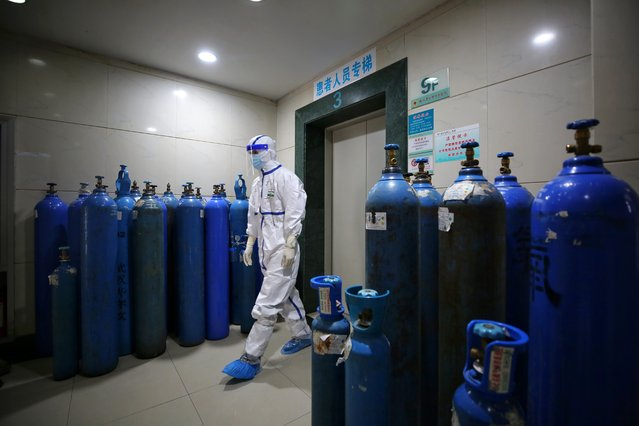 A medical worker walks by the oxygen canisters in a hospital designated for COVID-19 patients in Wuhan in central China's Hubei province Wednesday, March 11, 2020. (Photo by Feature China/Barcroft Media via Getty Images)