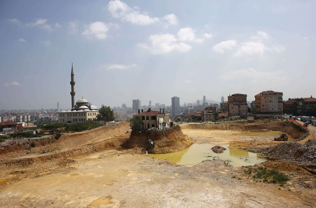 """A lone house is seen at the construction site of an urban transformation project in Fikirtepe, an Istanbul neighborhood in the Asian part of the city, August 14, 2014. The house, known as """"Lone house"""", belongs to a family who had refused to allow its demolition, bringing the project to a standstill for months. (Photo by Murad Sezer/Reuters)"""