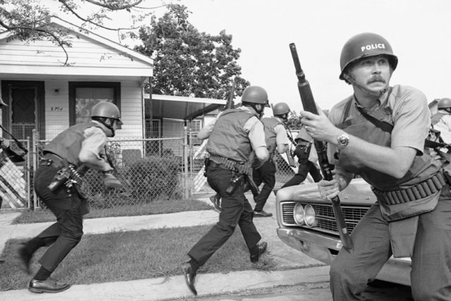 New Orleans police officers try to keep their heads down as they move in on a Black Panther headquarters during an exchange of gunfire in New Orleans on September 15, 1970. The shootout occurred as police moved in to make arrests on Tuesday morning following a series of incidents. (Photo by Jack Thornell/AP Photo)