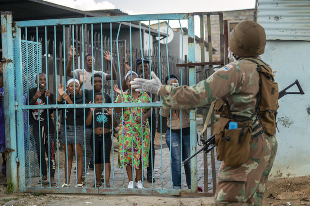 South African National Defense Forces patrol the densely populated Alexandra township east of Johannesburg Friday, March 27, 2020. South Africa went into a nationwide lockdown for 21 days in an effort to mitigate the spread to the coronavirus, but in Alexandra, many people were gathering in the streets disregarding the lockdown. (Photo by Jerome Delay/AP Photo)
