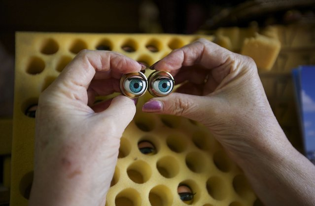 Australian doll repairer Kerry Stuart, a 25-year veteran at Sydney's Doll Hospital, matches a pair of eyes from her stock to be inserted into a customer's doll undergoing repairs, June 17, 2014. (Photo by Jason Reed/Reuters)