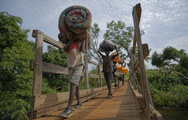 In this Thursday, June 8, 2017 file photo, from left to right, South Sudanese refugees Thomas Wani, 12, brother Peter Lemi, 14, mother Rose Sunday, and father Julius Lezu, cross a wooden bridge from South Sudan to Uganda at the Busia crossing, near Kuluba, in northern Uganda. (Photo by Ben Curtis/AP Photo)