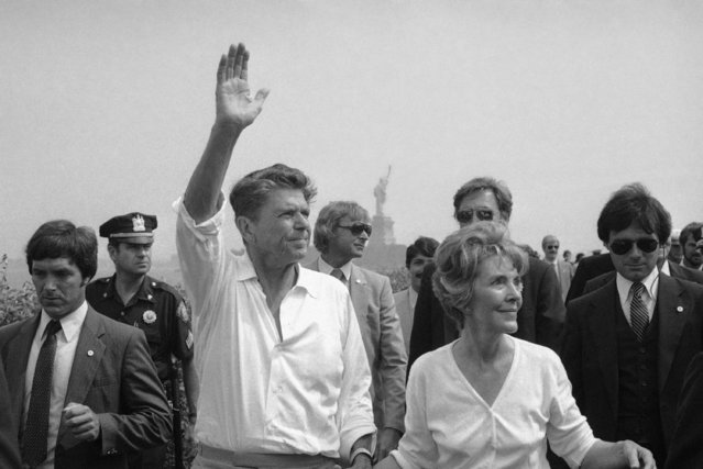 Ronald Reagan waves to crowd as wife Nancy Reagahn  walks along in Liberty Park in Jersey City, New Jersey  Monday, September 2, 1980. Reagan was in the area for Labor Day campaigning. Background shows the Statue of Liberty. (Photo by AP Photo/Cabrera)