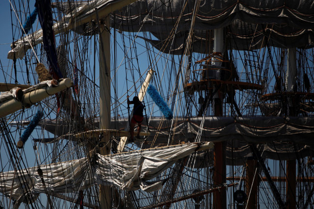 Crew members prepare a ship before the beginning of the Tall Ships Races 2016 parade, in Lisbon, Portugal, July 25, 2016. (Photo by Pedro Nunes/Reuters)