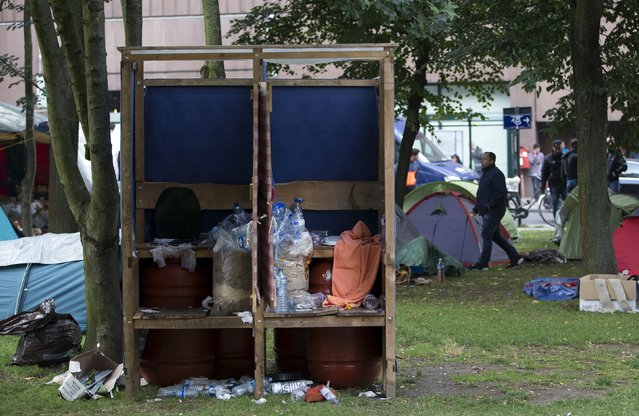 An asylum seeker walks behind makeshift sanitary in a camp outside the foreign office in Brussels, Belgium September 3, 2015. (Photo by Yves Herman/Reuters)