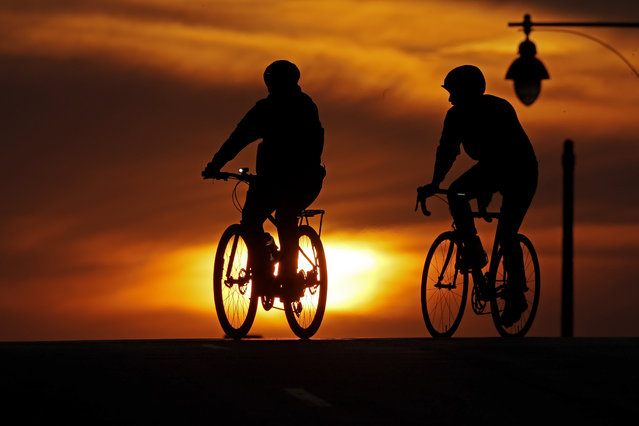 A pair of cyclists cross an empty downtown street as the sun sets Wednesday, April 1, 2020, in Kansas City, Mo. (Photo by Charlie Riedel/AP Photo)