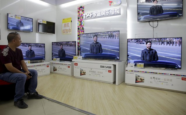 A man watches the televisions showing live broadcast of China's President Xi Jinping inspecting the army during a military parade marking the 70th anniversary of the end of World War Two, at a home appliances store in Wuhan, Hubei province, China, September 3, 2015. (Photo by Darley Shen/Reuters)
