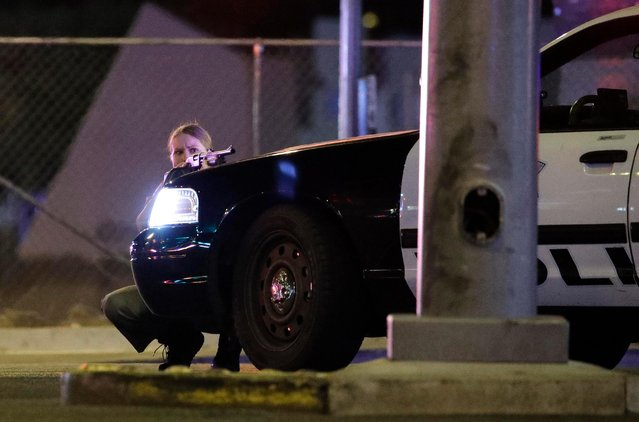 A police officer takes cover behind a police vehicle during a shooting near the Mandalay Bay resort and casino on the Las Vegas Strip, Sunday, October 1, 2017, in Las Vegas. (Photo by John Locher/AP Photo)