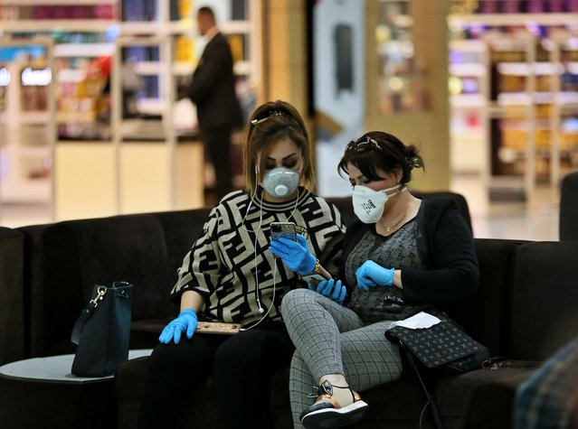 Passengers wear protective masks while waiting for their plane in Baghdad Airport, Iraq, Wednesday, March 4, 2020. From religion to sports, countries were taking drastic and increasingly visible measures to curb the new coronavirus that first emerged in China and was spreading quickly through Europe, the Mideast and the Americas. (Photo by Hadi Mizban/AP Photo)