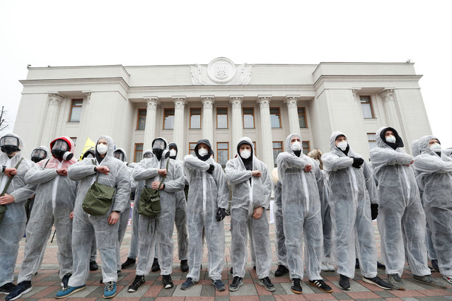 Activists of the National Corps political party wearing protective gear take part in a rally demanding to quarantine lawmakers amid coronavirus disease (COVID-19) concerns, in front of the Ukrainian parliament building in Kiev, Ukraine on March 17, 2020. (Photo by Valentyn Ogirenko/Reuters)