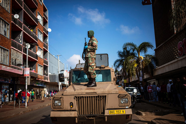 A member of the South African National Defense Force (SANDF) stands on a military vehicle during a joint South African Police Services (SAPS) and SANDF patrol on day 31 of the national lockdown as a result of the ongoing coronavirus COVID-19 pandemic in Johannesburg, South Africa, 26 April 2020. The patrol was in the high density areas of Hillbrow and Yoeville where civilians are still breaking the strict lockdown rules. Those that where breaking the rules where arrested. South Africa's Stage 5 lockdown is due to end 30 April 2020 when stage 4 will be implemented. (Photo by Kim Ludbrook/EPA/EFE)