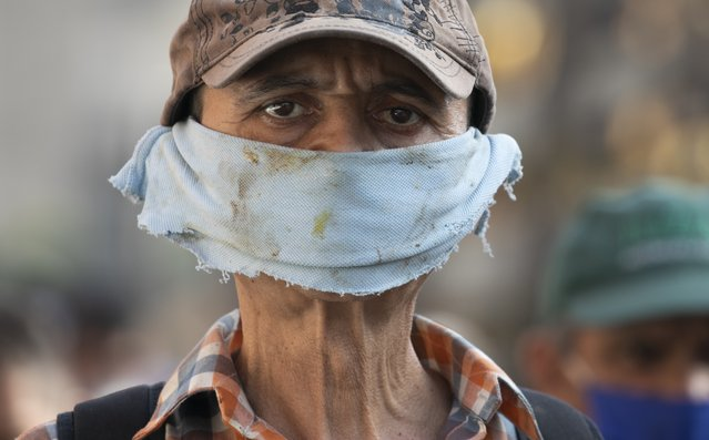 A man wears a piece of cloth as a face mask to avoid spread of the new coronavirus at a street market in Caracas, Venezuela, Friday, April 10, 2020. (Photo by Ariana Cubillos/AP Photo)