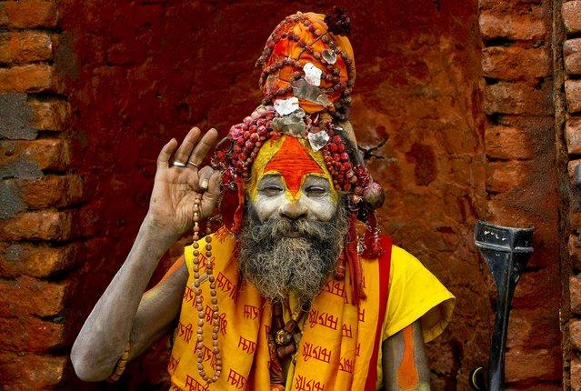 A Hindu holy man waves to camera at the Pashupatinath temple during Teej festival celebrations in Katmandu, Nepal, on September 18, 2012. (Photo by Binod Josh/Associated Press)