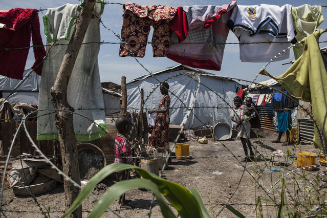 A woman washes clothes in the Protection of Civilians (POC) site at the United Nations Mission in South Sudan (UNMISS) compound in Malakal, South Sudan on Saturday, July 9, 2016. (Photo by Jane Hahn/The Washington Post)