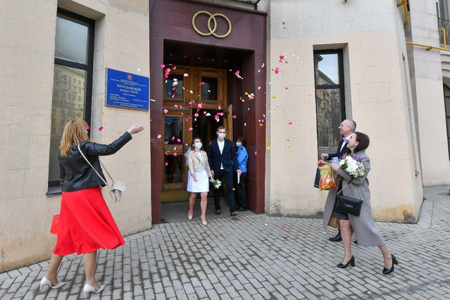 Guests congratulate a newly-wed couple outside a marriage registration building in Moscow, Russia, April 8, 2020. (Photo by Sergei Kiselyov/Moscow News Agency via Reuters)
